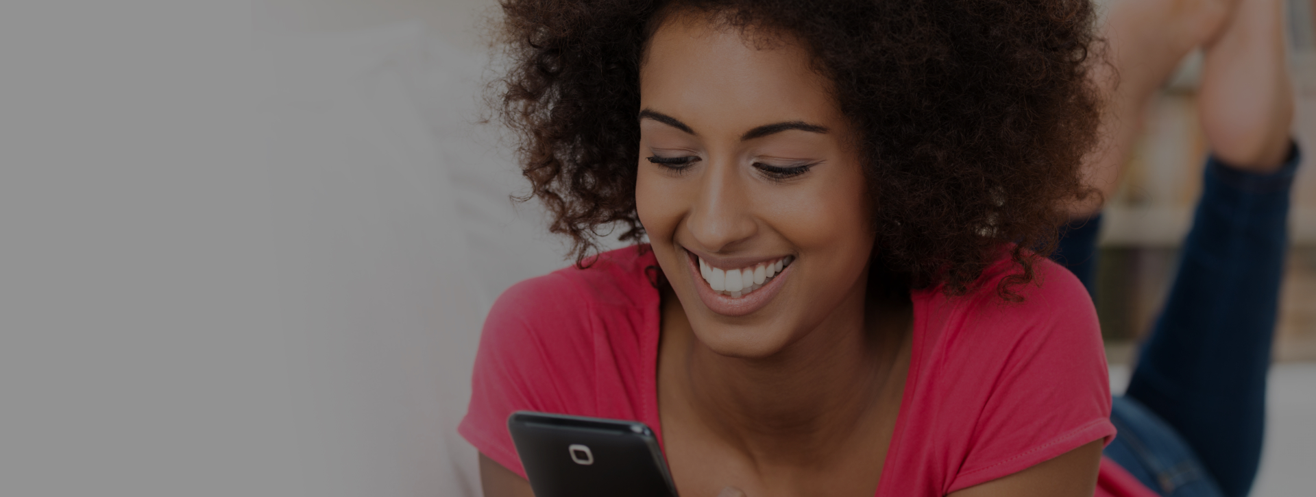 woman smiling while texting