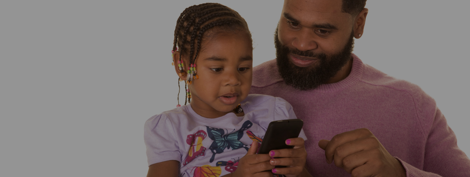 fahter and daughter using a smartphone
